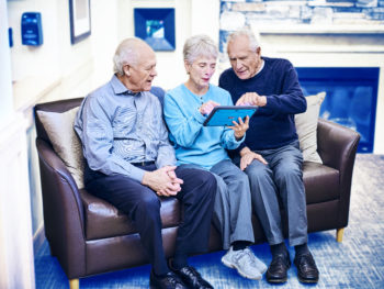 Residents engaging with content on a senior-friendly tablet