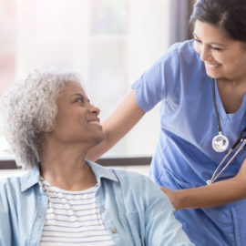 A skilled nurse interacting with a senior living community resident