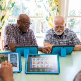 Older adults enjoying iN2L tablets.