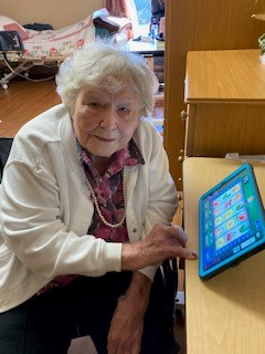 Woman in nursing home enjoying a game on an iN2L tablet.