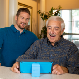 A caregiver is helping a senior learn how to use the iN2L tablet
